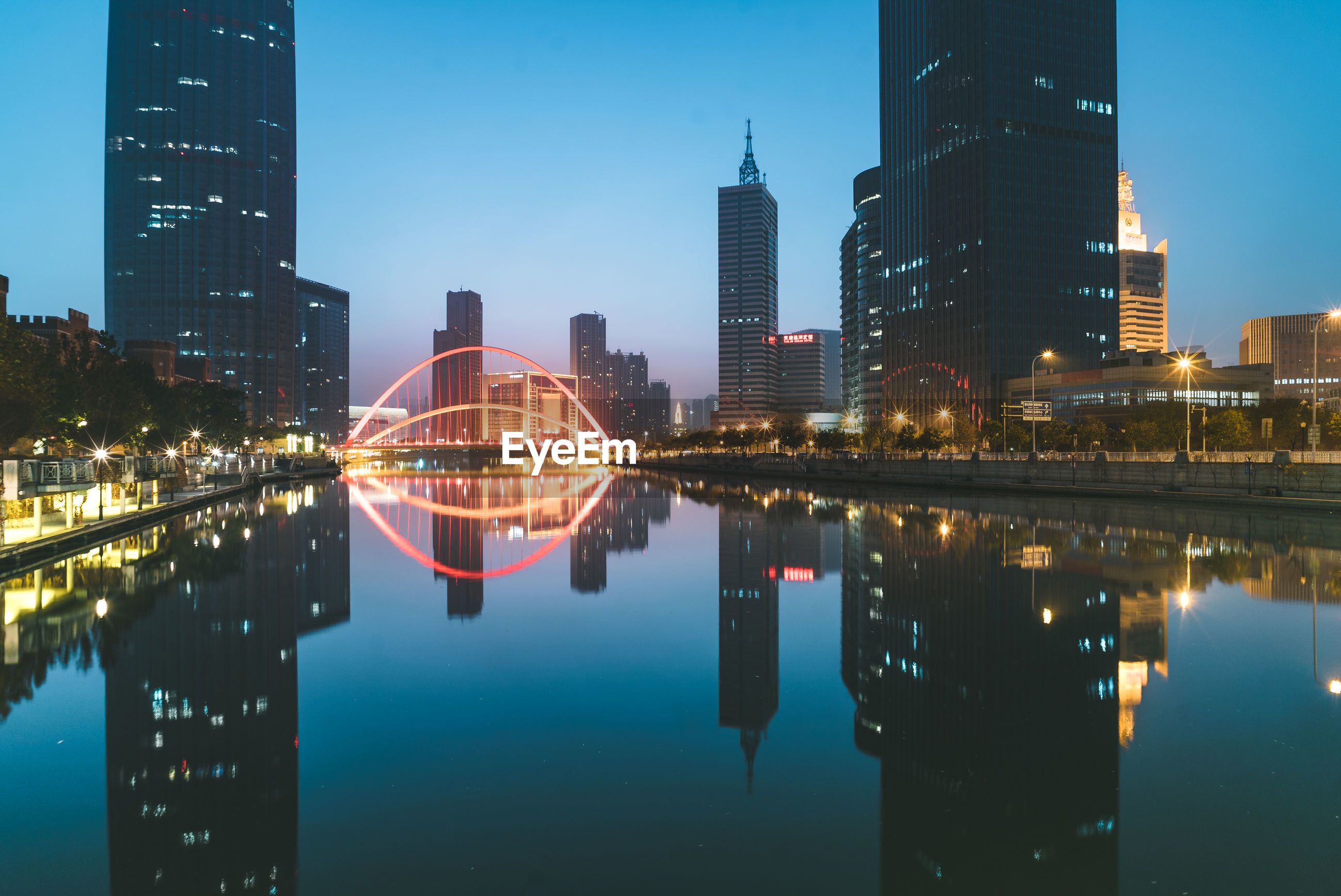 REFLECTION OF ILLUMINATED MODERN BUILDINGS IN CITY