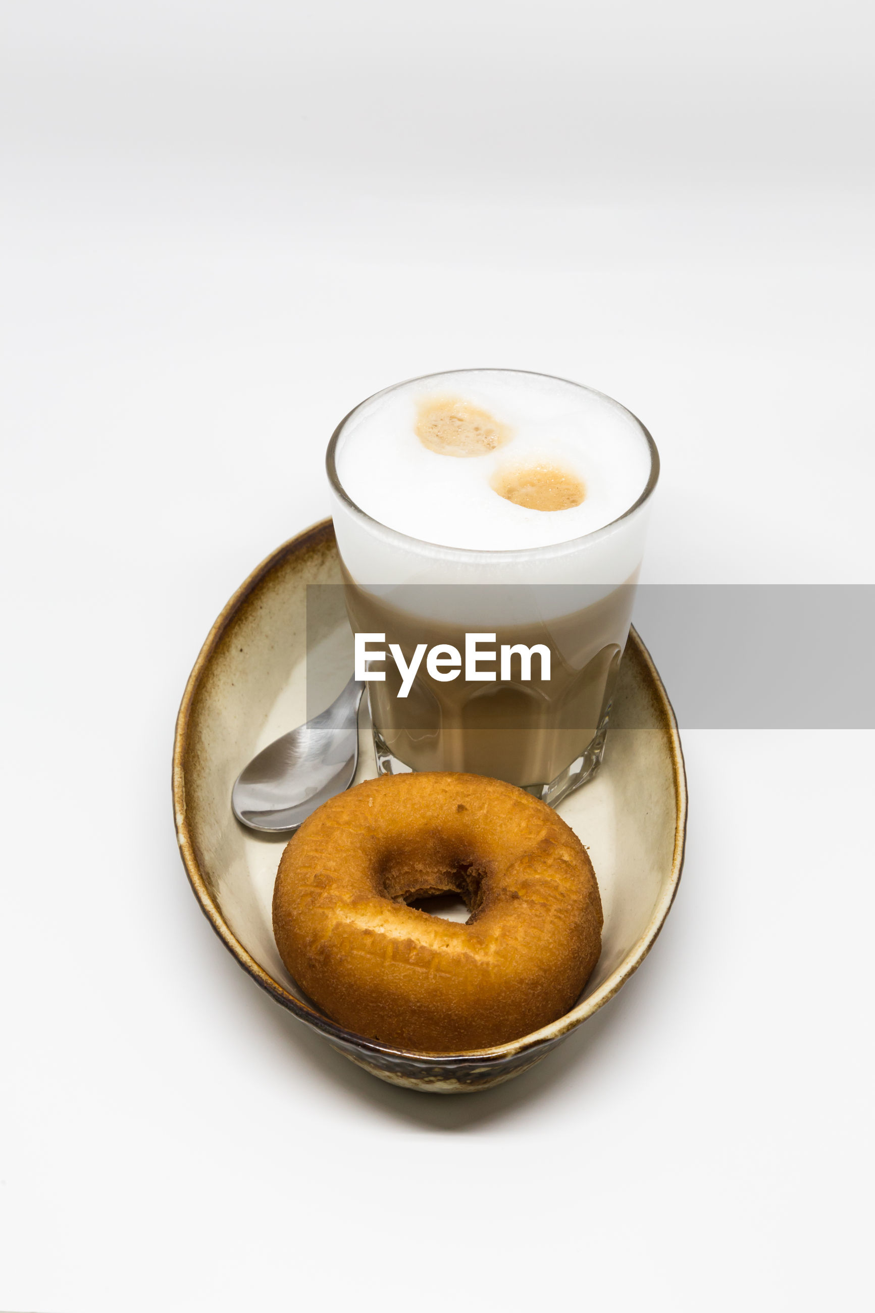 High angle view of donut and coffee in tray against white background
