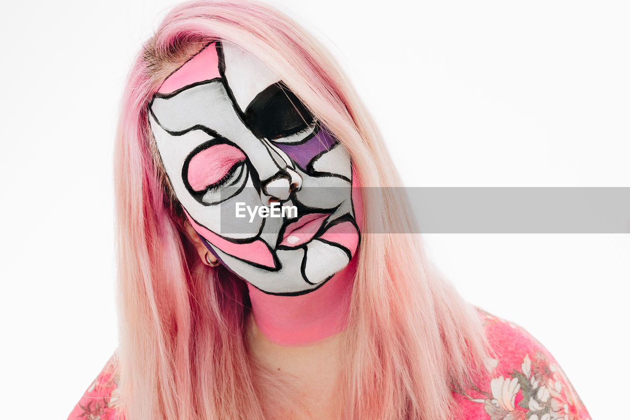 Close-Up Of Woman With Face Paint Against White Background