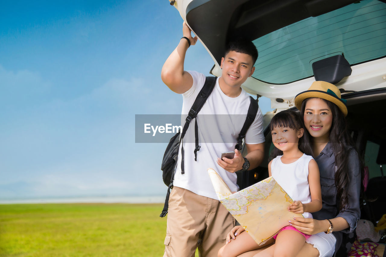 Happy family reading map while sitting in car trunk on field against sky