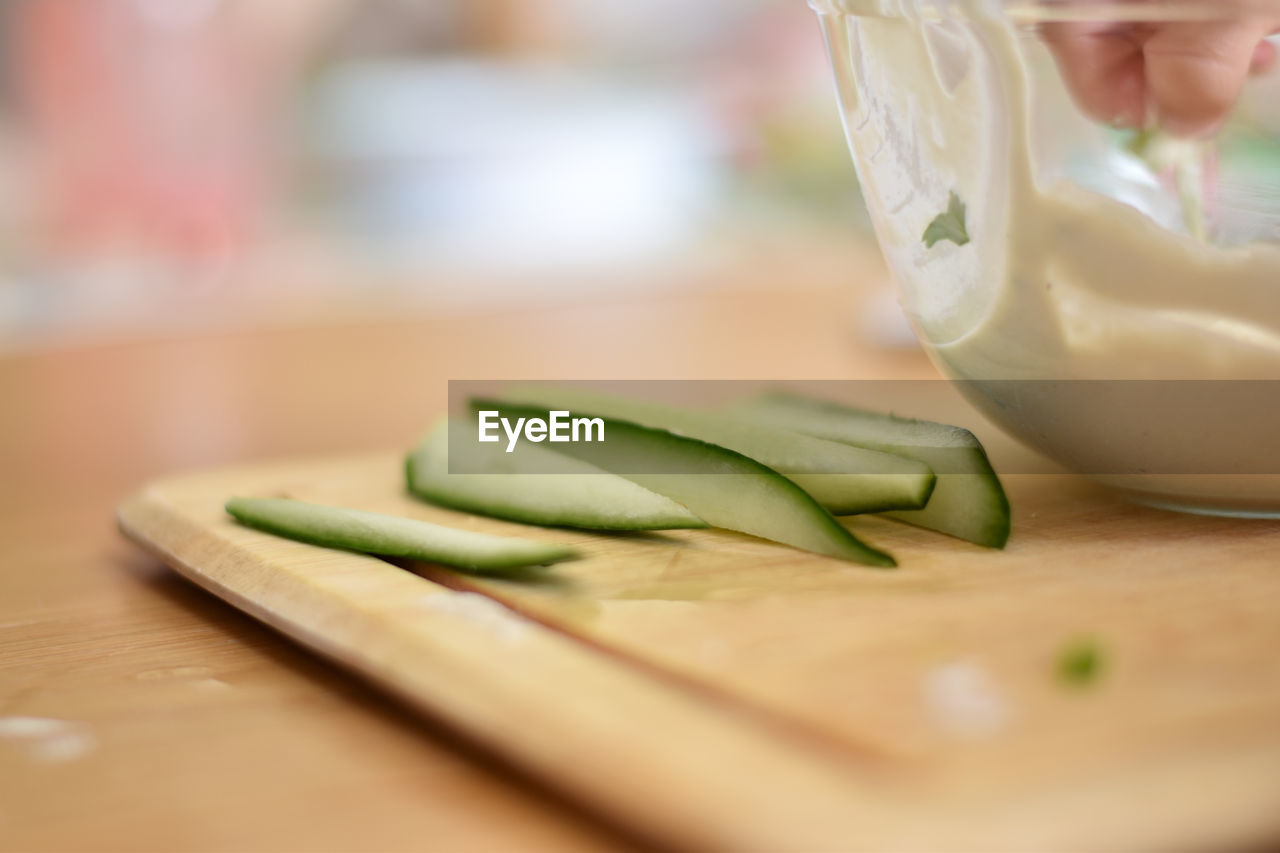 food and drink, freshness, food, table, close-up, selective focus, indoors, wood - material, vegetable, healthy eating, wellbeing, human hand, cutting board, focus on foreground, still life, green color, hand, real people, one person, human body part, finger, temptation