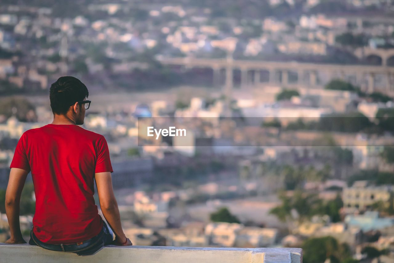 Young man wearing red t-shirt and eyeglasses looking at cityscape