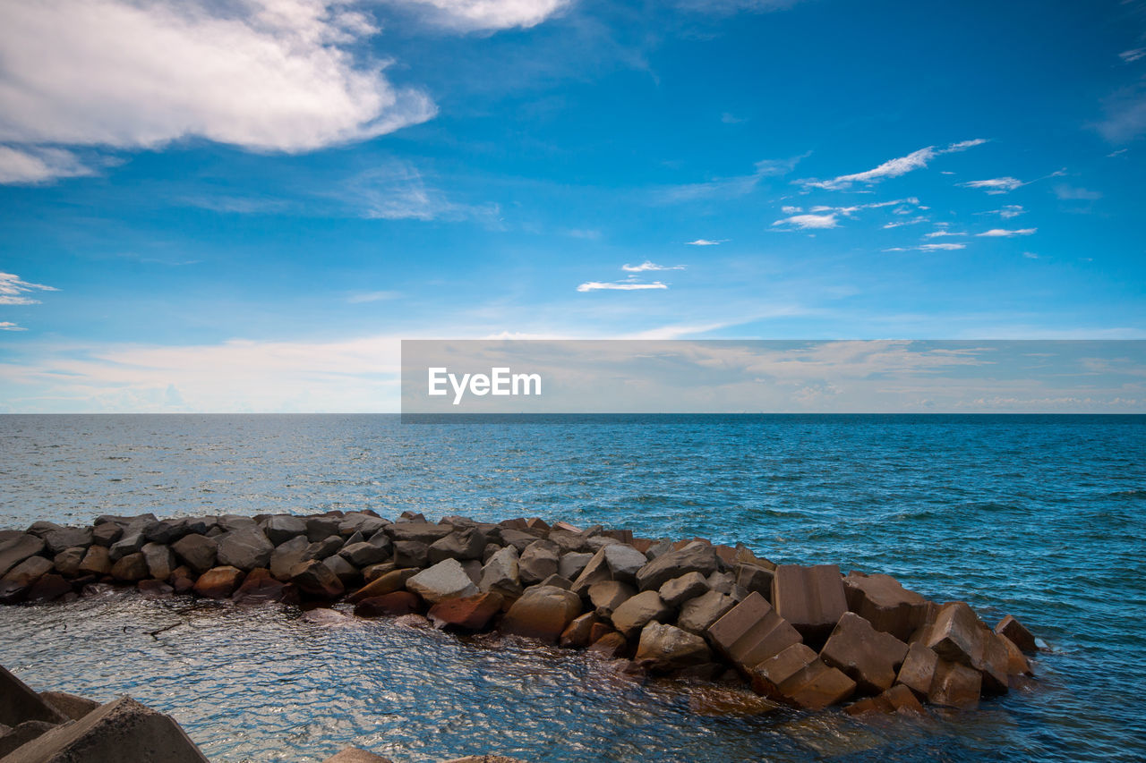 water, sky, sea, horizon over water, beauty in nature, horizon, cloud - sky, scenics - nature, rock, tranquility, nature, solid, tranquil scene, no people, day, blue, rock - object, idyllic, land, outdoors, groyne, pebble