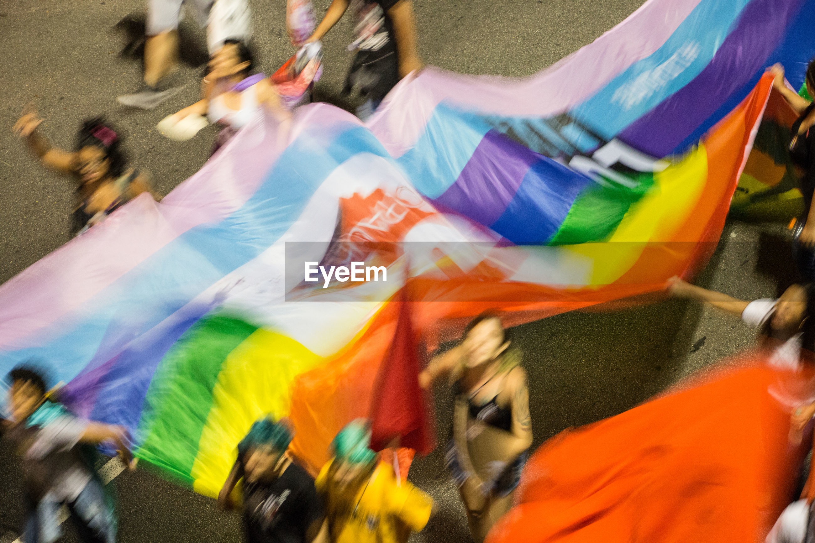 Blurred motion of people with rainbow flag walking on road during parade