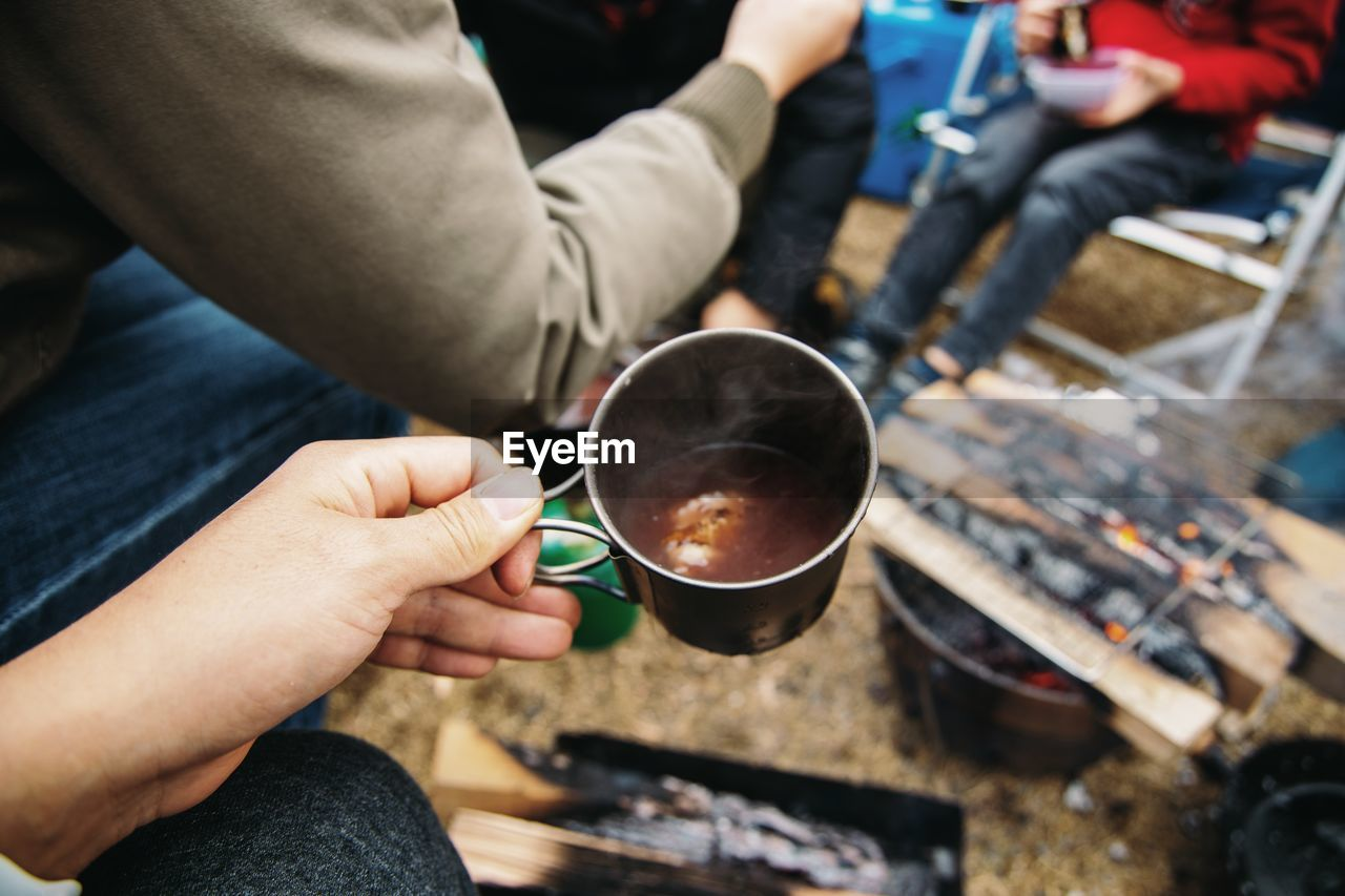 Cropped hand holding coffee at campsite