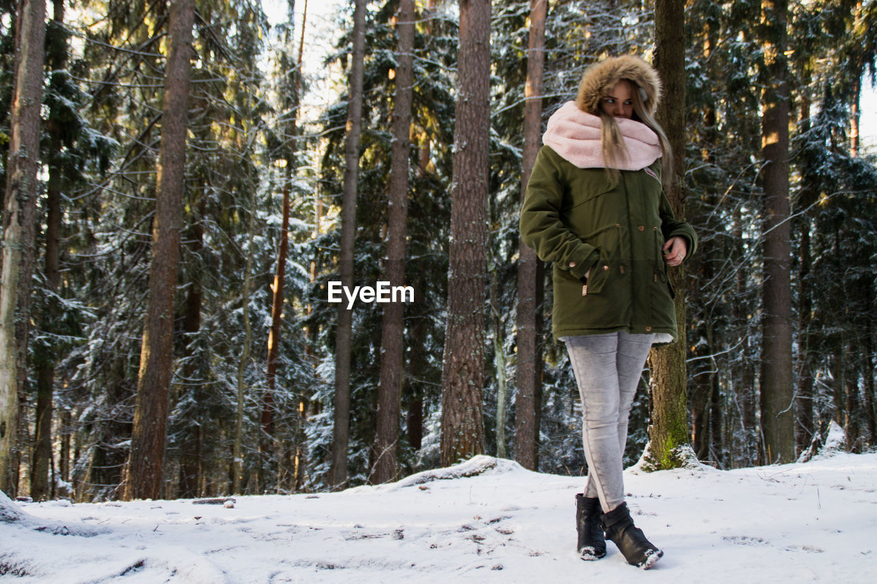 Woman standing at snow covered forest