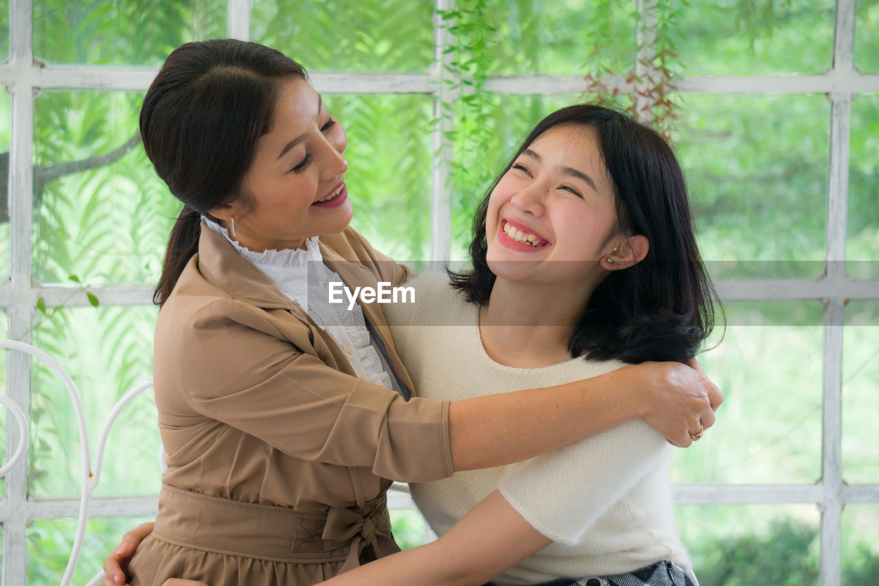 Cheerful mother and daughter embracing against window