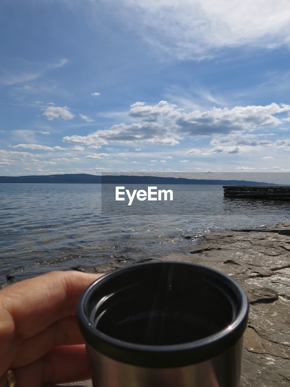 sky, hand, one person, human hand, human body part, water, holding, food and drink, cloud - sky, sea, real people, day, unrecognizable person, drink, refreshment, cup, mug, coffee, nature, body part, hot drink, outdoors, glass, finger, human limb