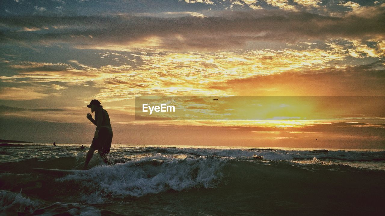 Side view of a man walking on beach at sunset