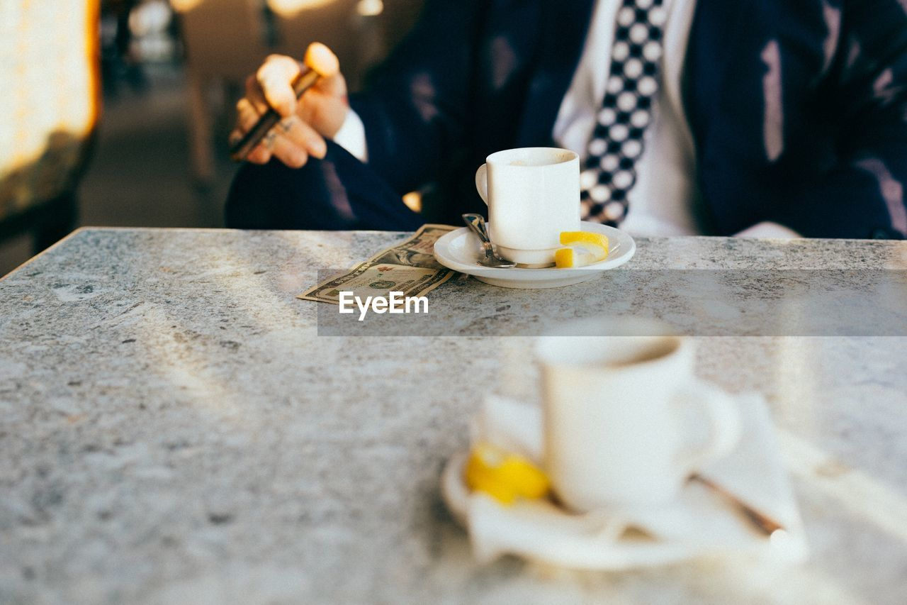 Midsection Of Businessman With Coffee On Table At Cafe
