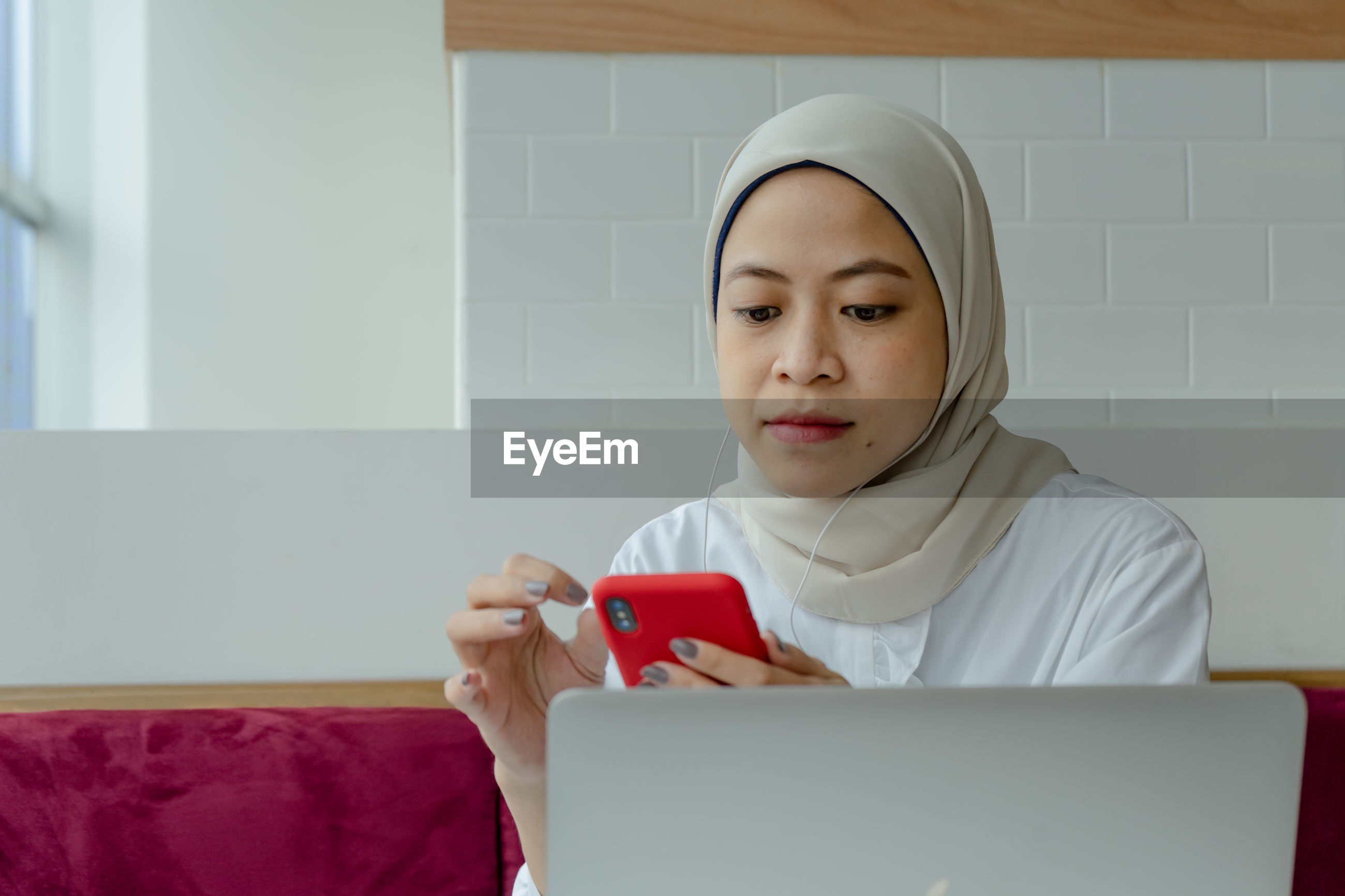 PORTRAIT OF YOUNG WOMAN USING MOBILE PHONE IN LAPTOP