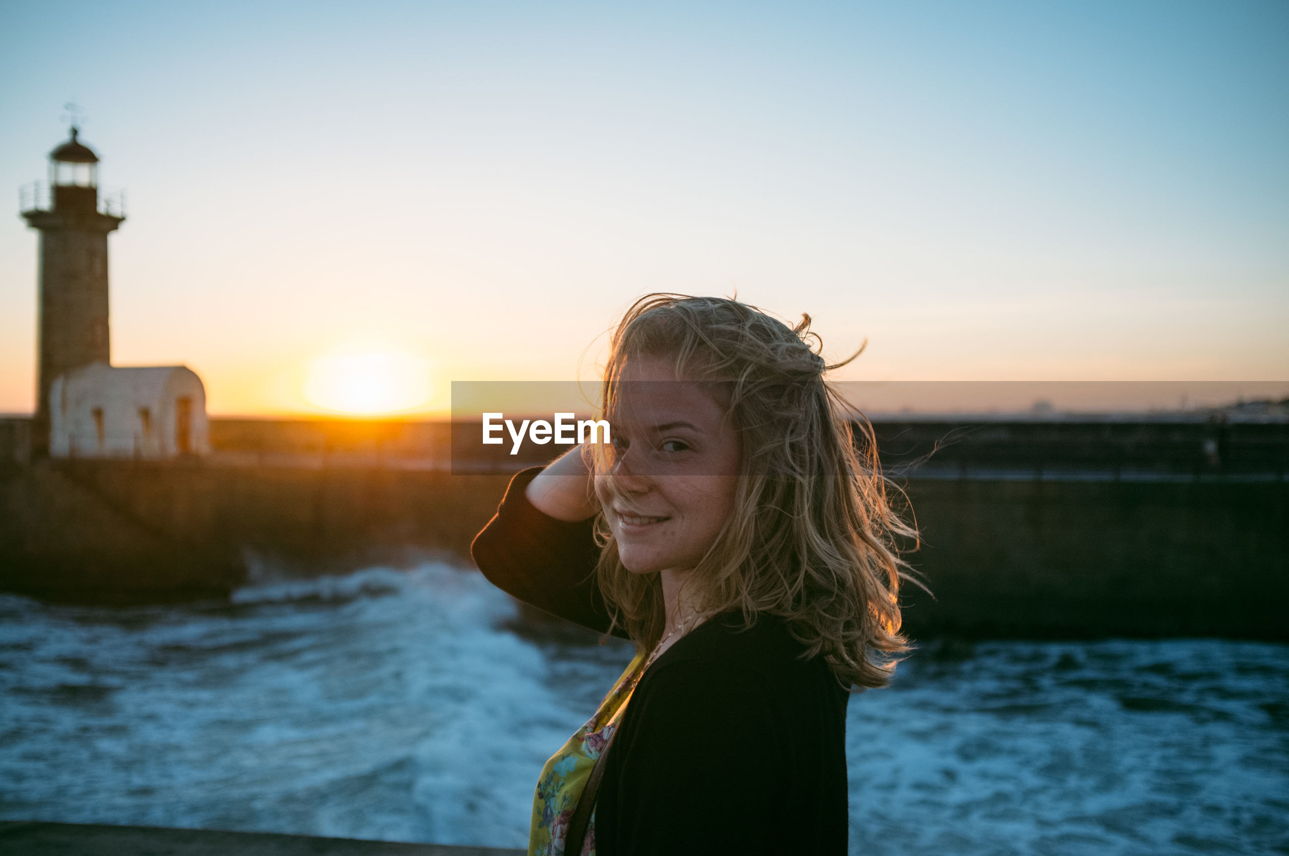 Portrait of young woman by sea at sunset