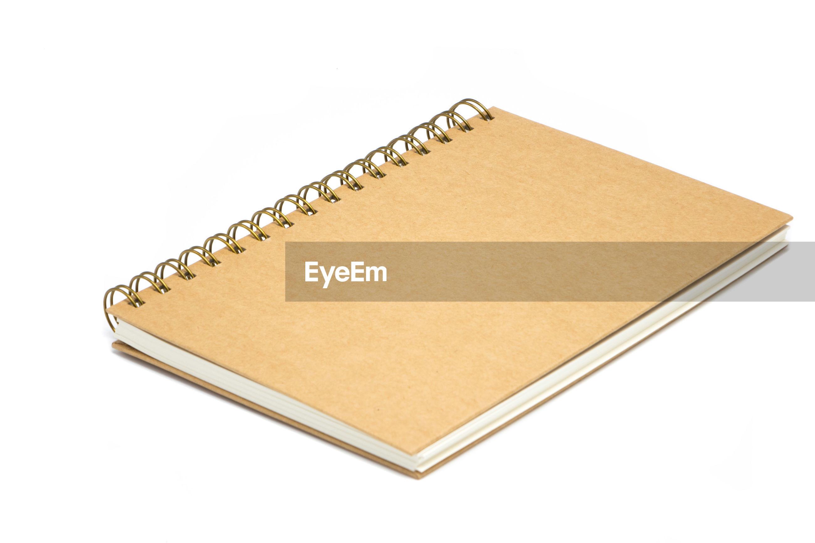 Brown spiral notebook over white background