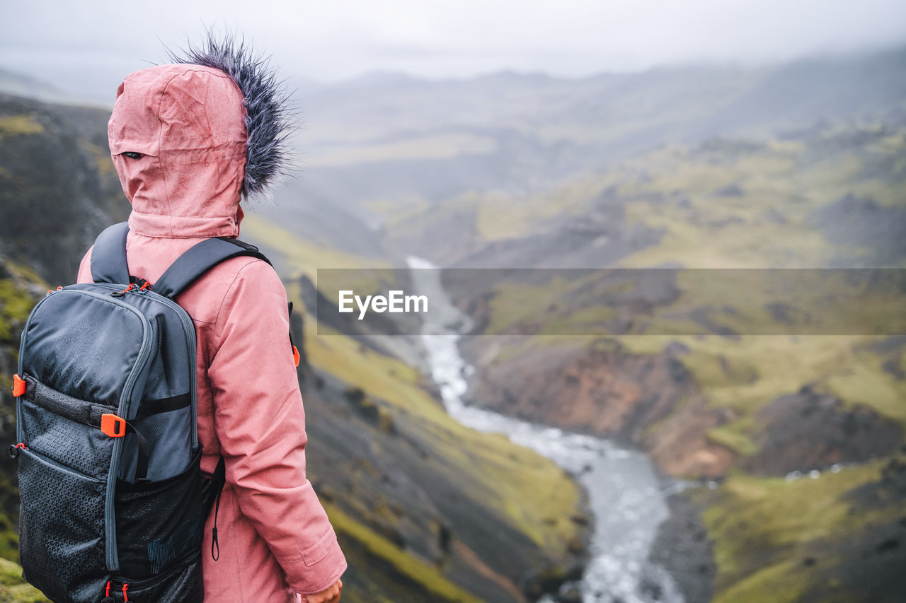 Woman with backpack enjoying icelandic river fossa close to haifoss waterfall in iceland
