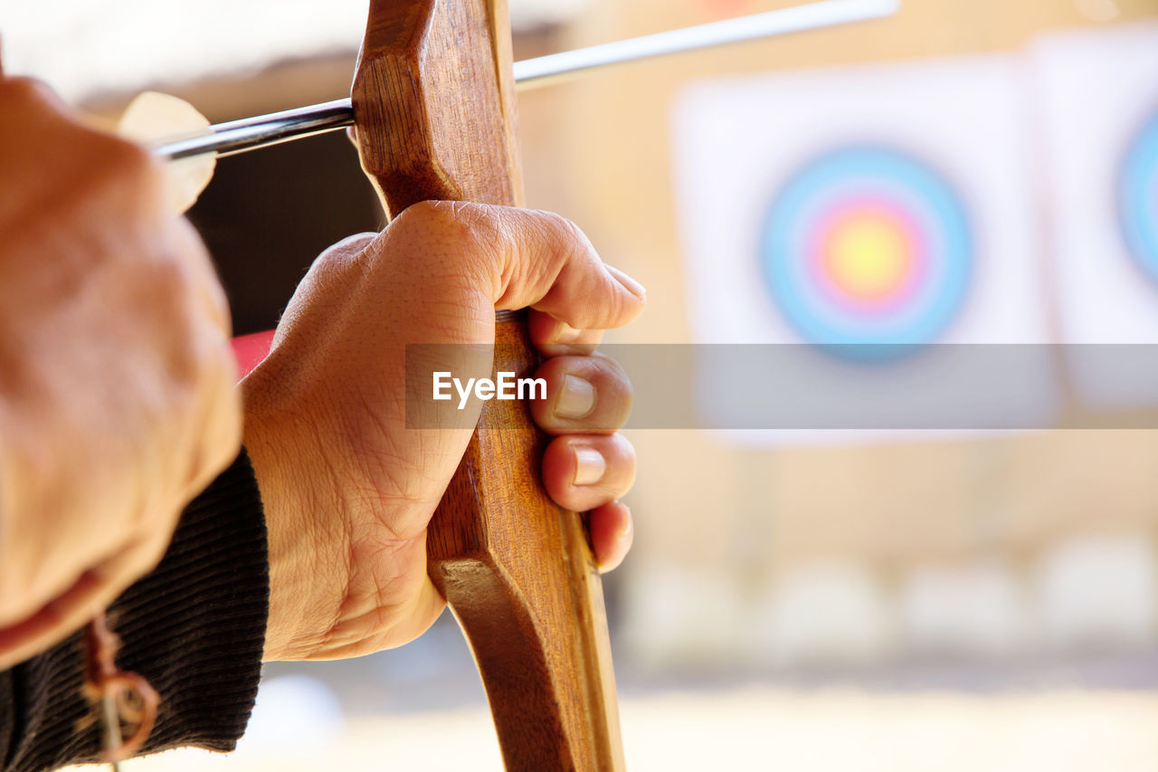 Close-Up Of Man With Bow And Arrow Aiming At Target
