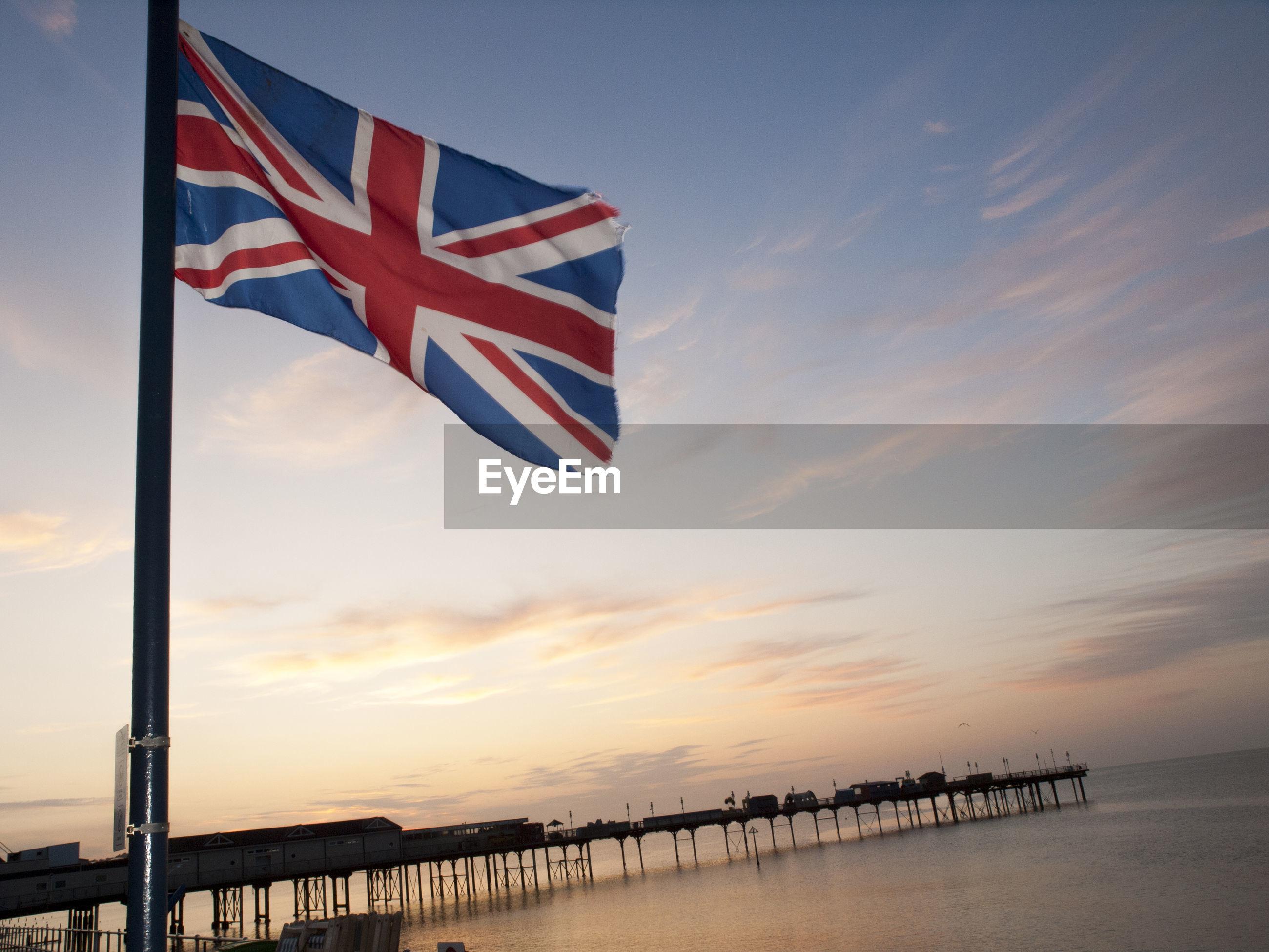 FLAG AGAINST SKY DURING SUNSET