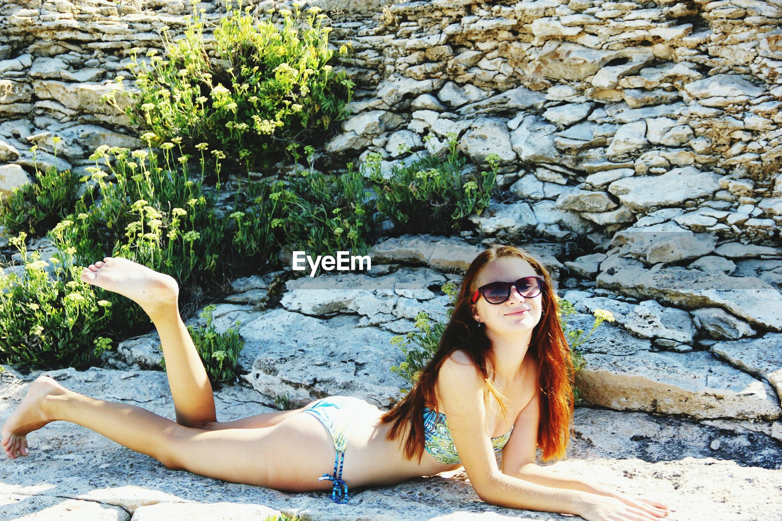 young adult, lifestyles, young women, leisure activity, person, water, portrait, rock - object, sitting, looking at camera, relaxation, casual clothing, high angle view, sunlight, day, long hair, vacations, full length