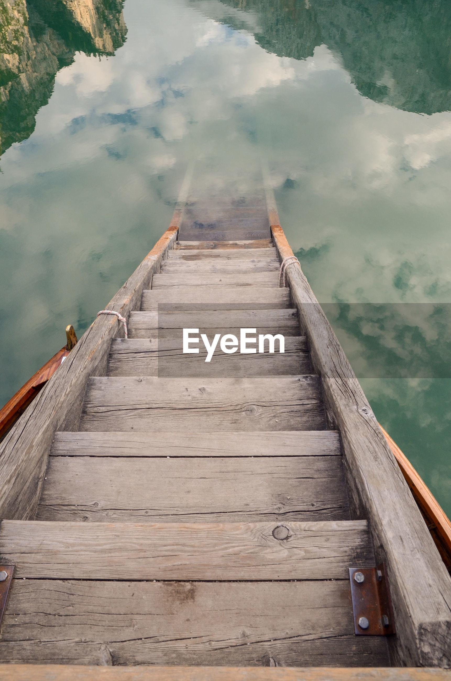 Surface level of wooden footbridge over pier against sky