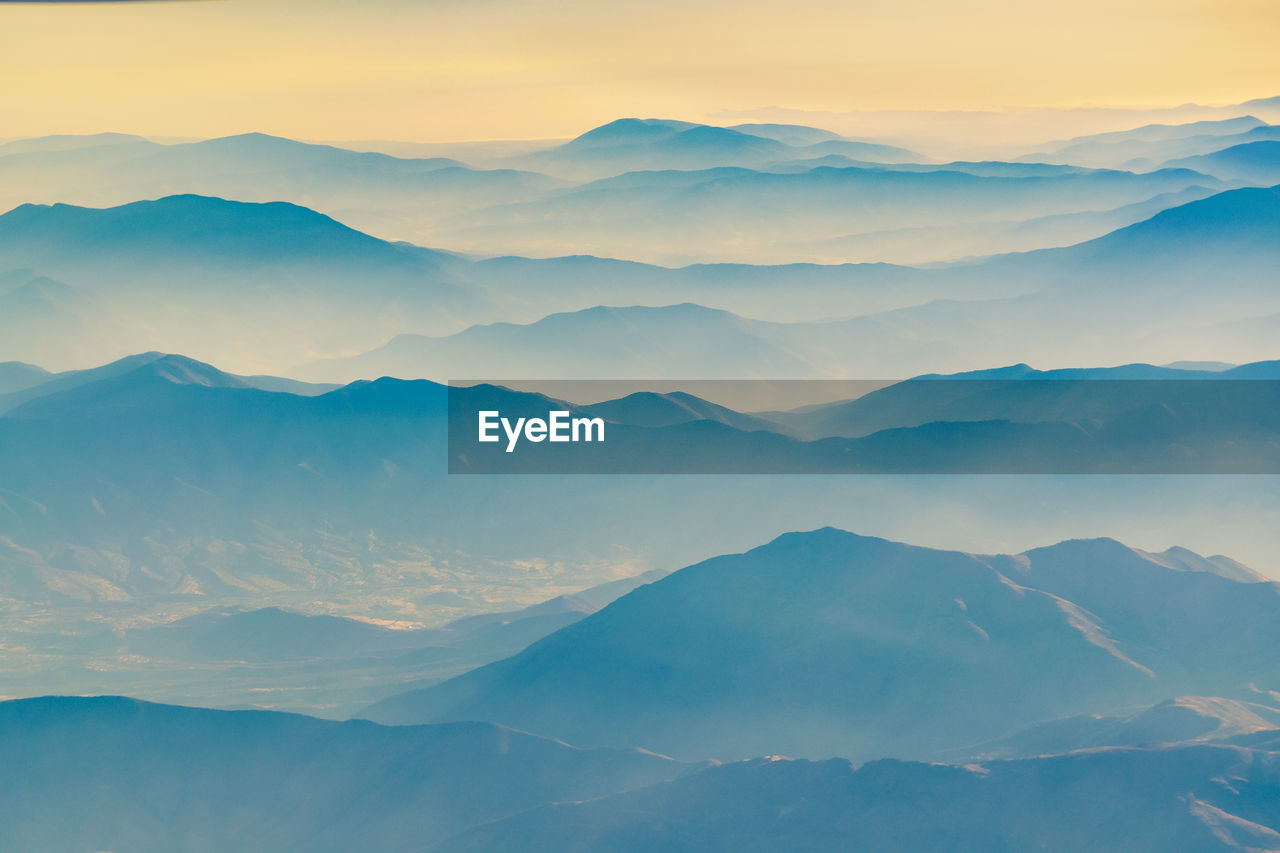 beauty in nature, mountain, scenics - nature, tranquil scene, tranquility, sky, no people, mountain range, non-urban scene, idyllic, nature, sunset, environment, remote, cloud - sky, landscape, outdoors, day, fog, mountain peak, hazy