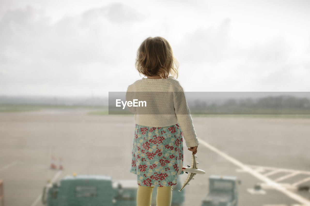 Rear view of child looking at airport runway against sky