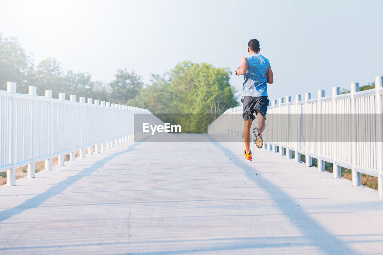 lifestyles, one person, full length, real people, the way forward, leisure activity, direction, men, rear view, casual clothing, diminishing perspective, footpath, day, railing, nature, wood - material, architecture, bridge, connection, outdoors, footbridge