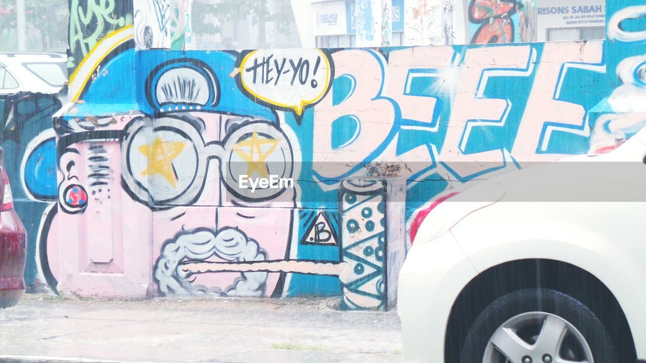 Car Parked By Graffiti Wall