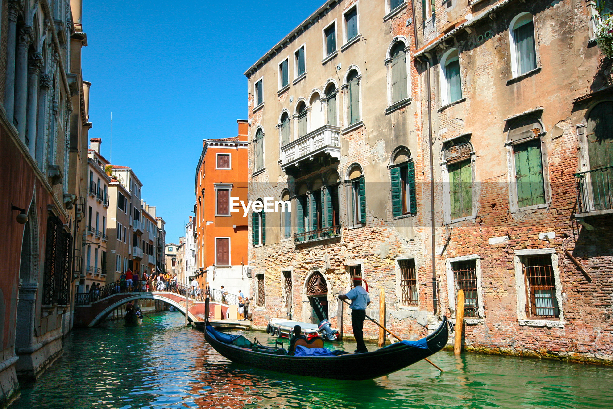 building exterior, cultures, architecture, gondola - traditional boat, travel destinations, built structure, canal, men, city, outdoors, gondolier, people, adults only, real people, water, adult, day, only men