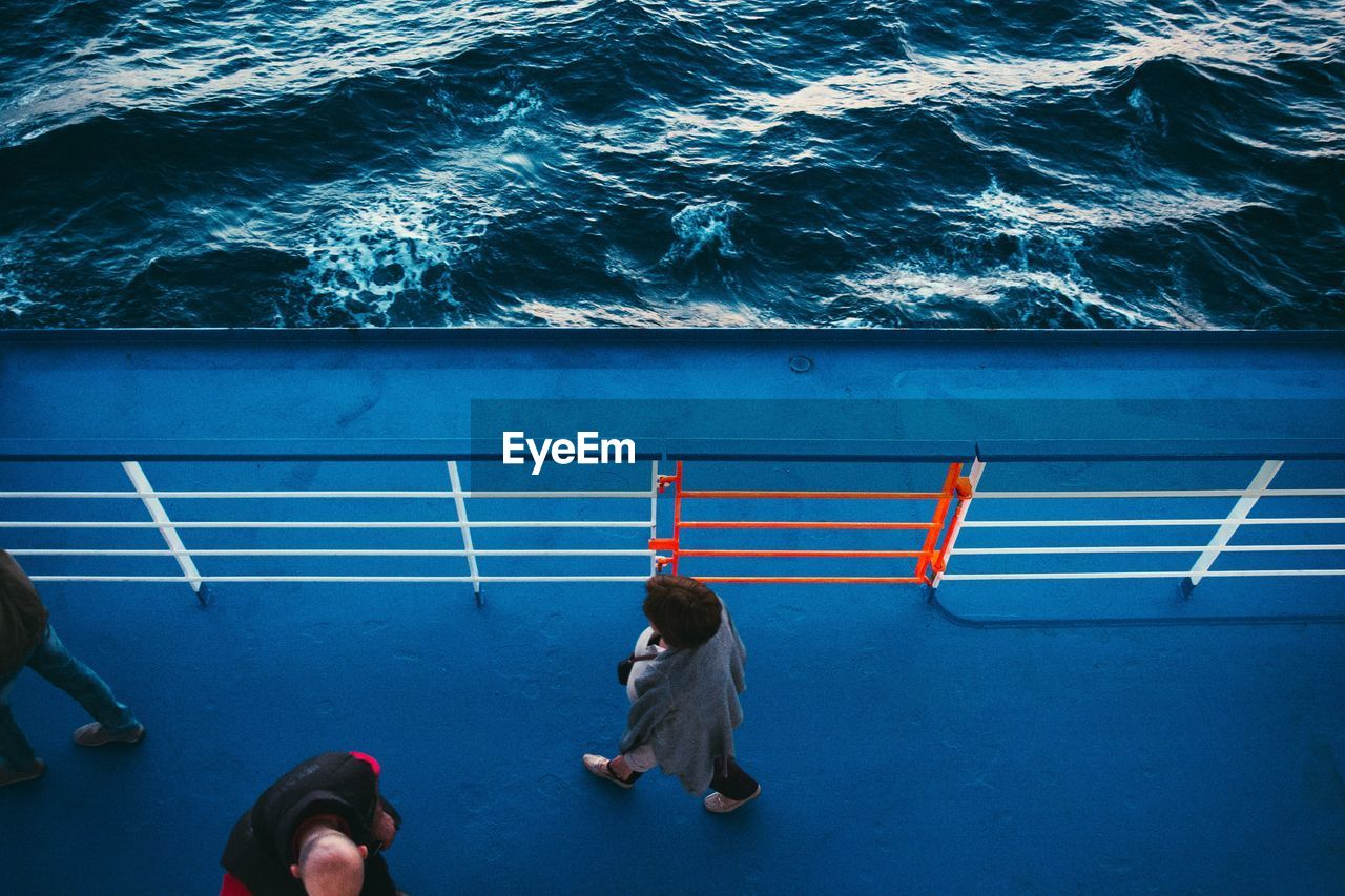 Directly Above Shot Of People Walking On Ferry Over Sea