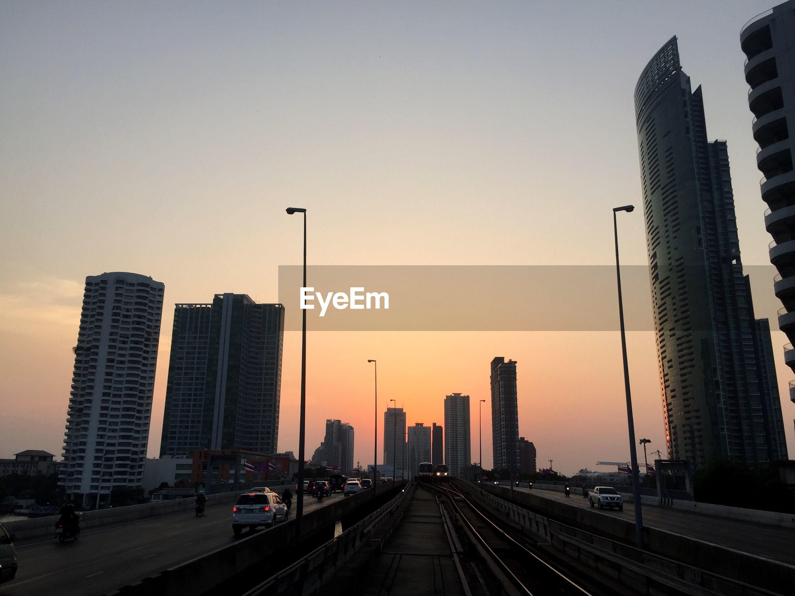 Railroad tracks amidst elevated roads in city during sunset