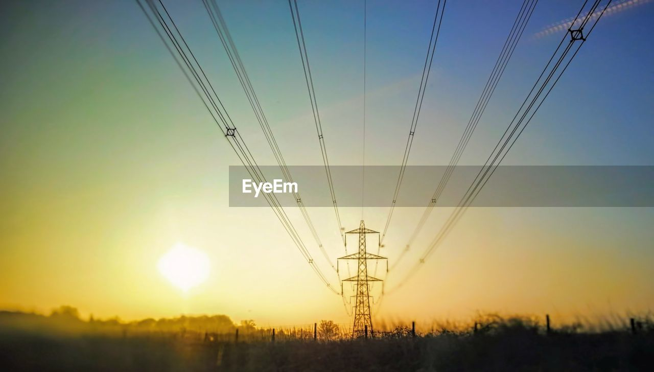 sky, sunset, fuel and power generation, technology, nature, cable, electricity pylon, power supply, electricity, orange color, environment, sun, transportation, power line, field, connection, landscape, air vehicle, outdoors, low angle view