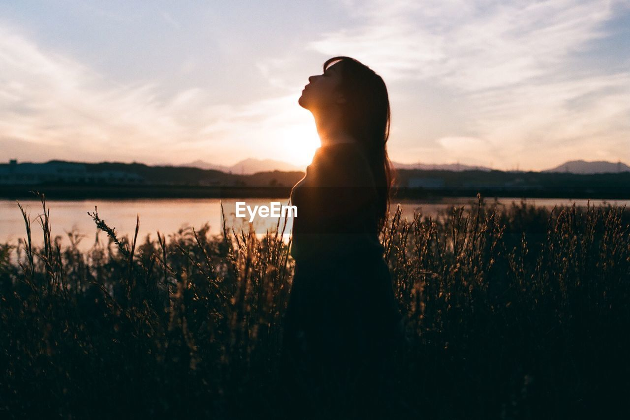 sunset, silhouette, nature, one person, beauty in nature, real people, standing, sky, field, plant, growth, tranquil scene, scenics, tranquility, outdoors, rear view, women, lifestyles, landscape, water, flower, grass, day, young adult, people