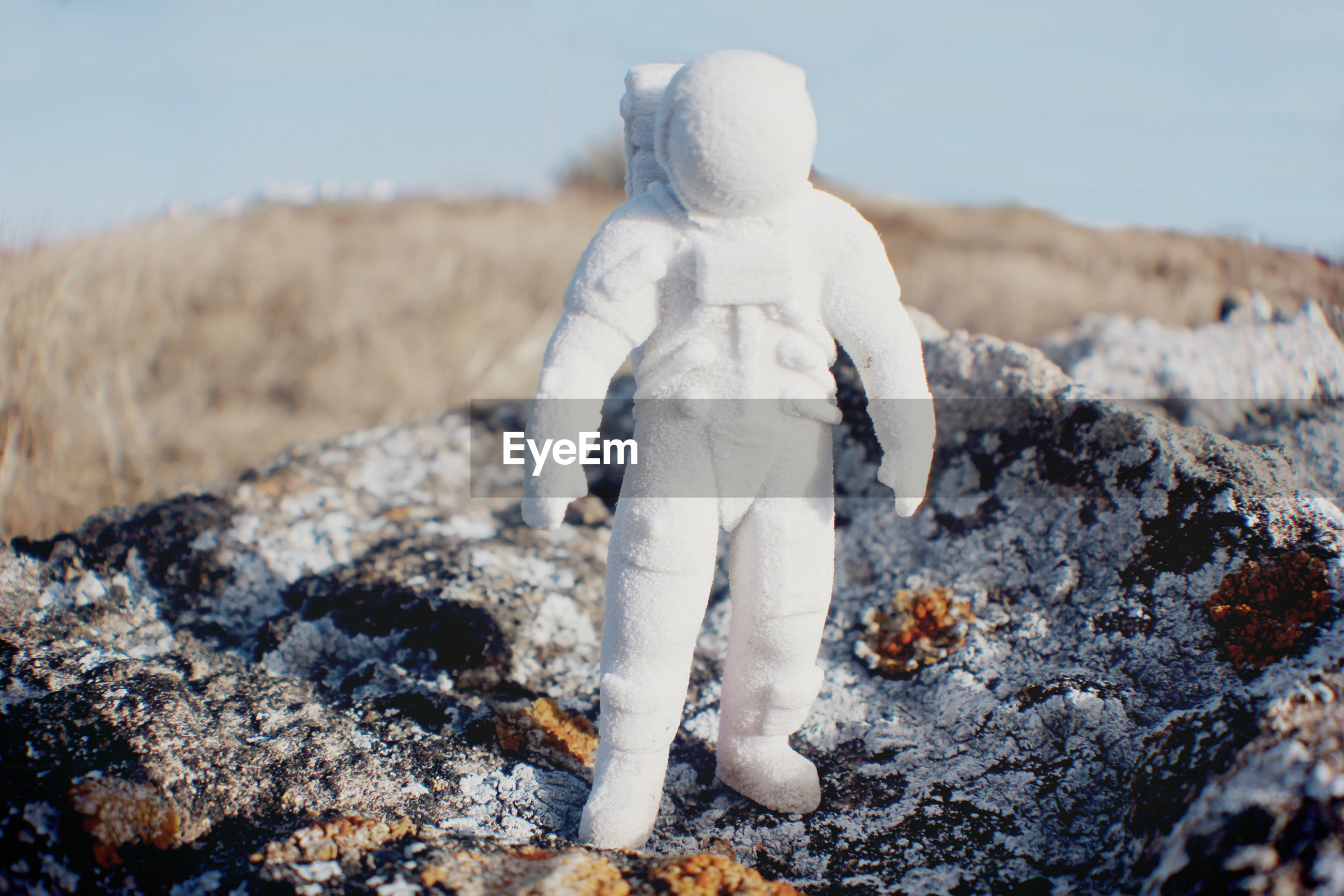 Close-up of white astronaut figurine on field