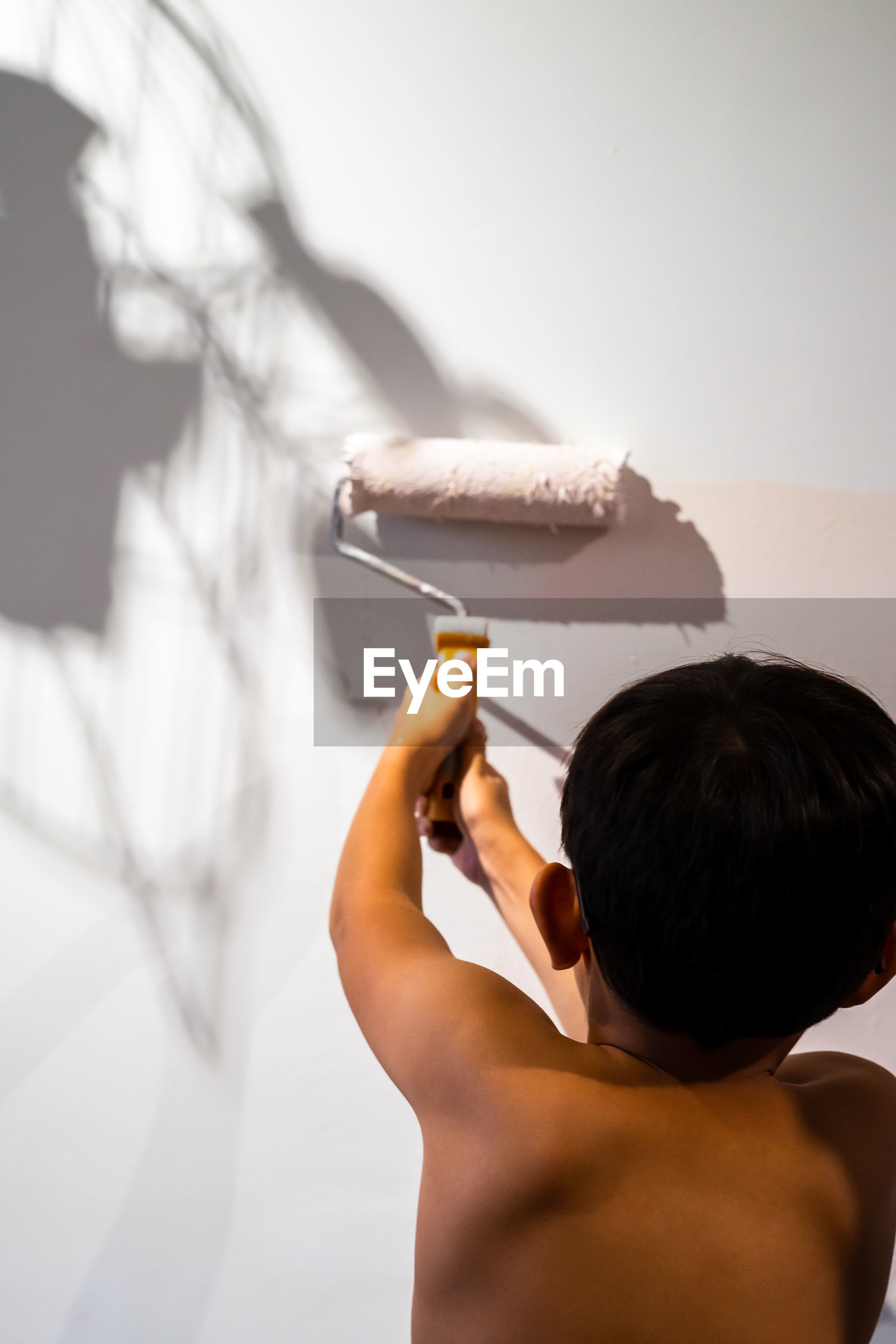 Rear view of shirtless boy holding paint roller on wall