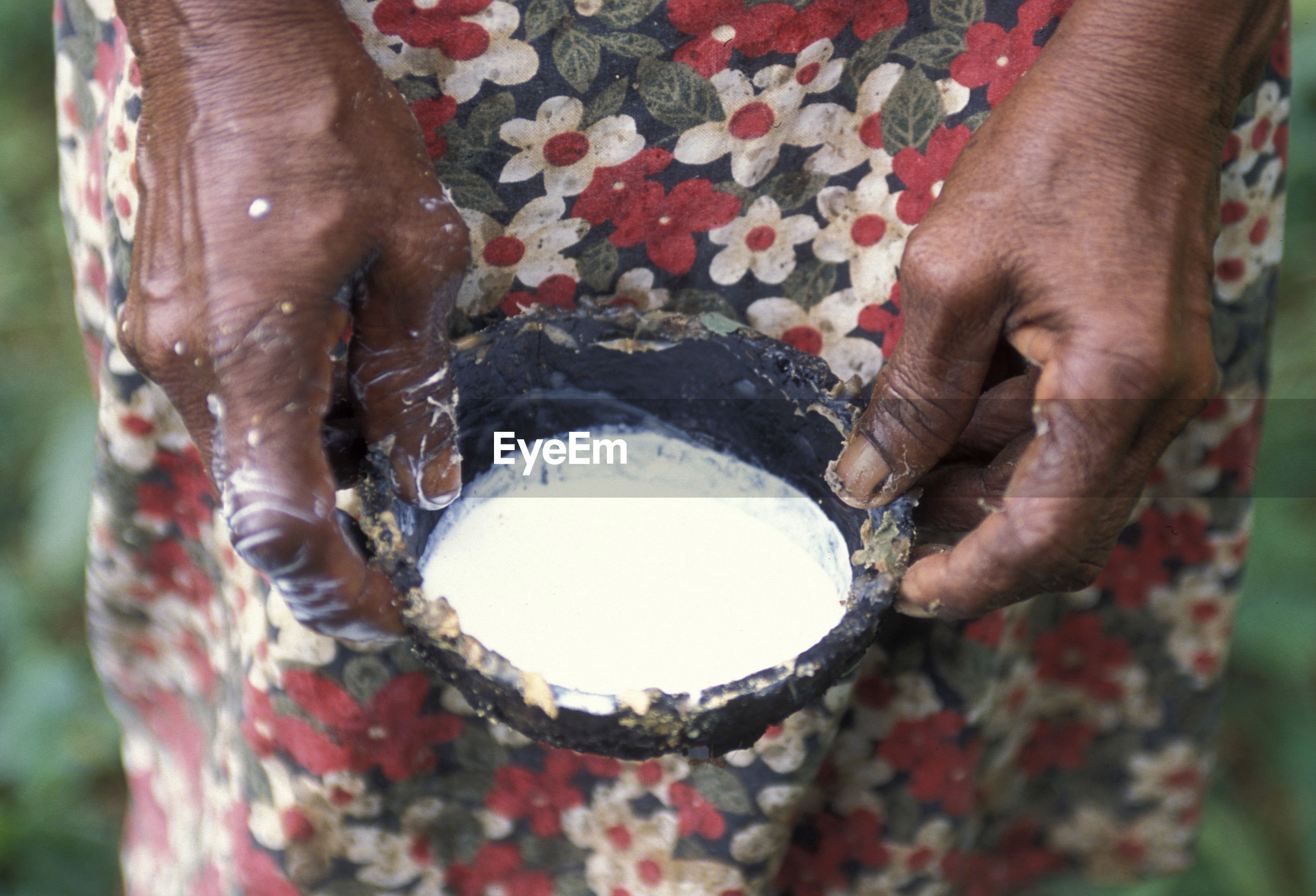 Midsection of woman holding rubber sap in bowl