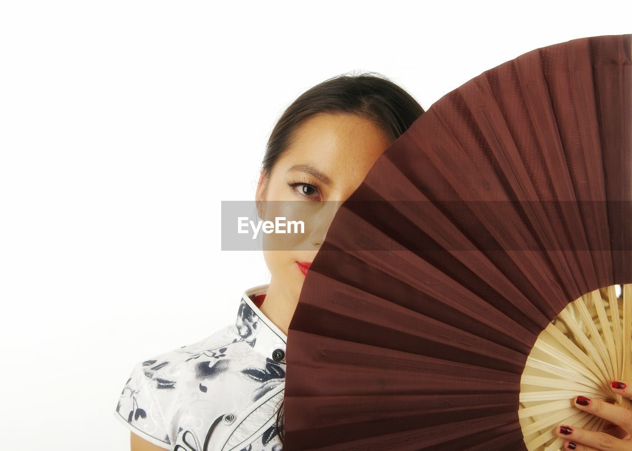 Cropped Portrait Of Woman Holding Folding Fan Against White Background