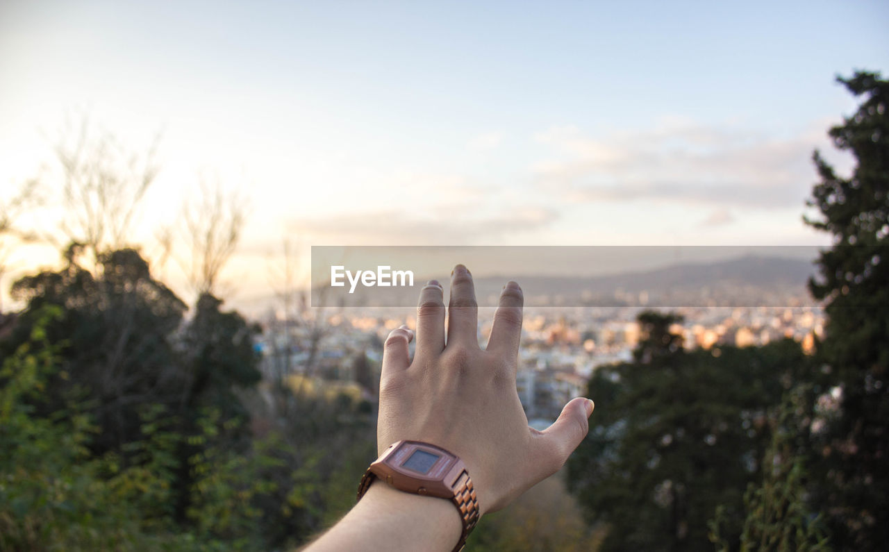 Cropped Image Of Hand Against Residential District And Sky During Sunset