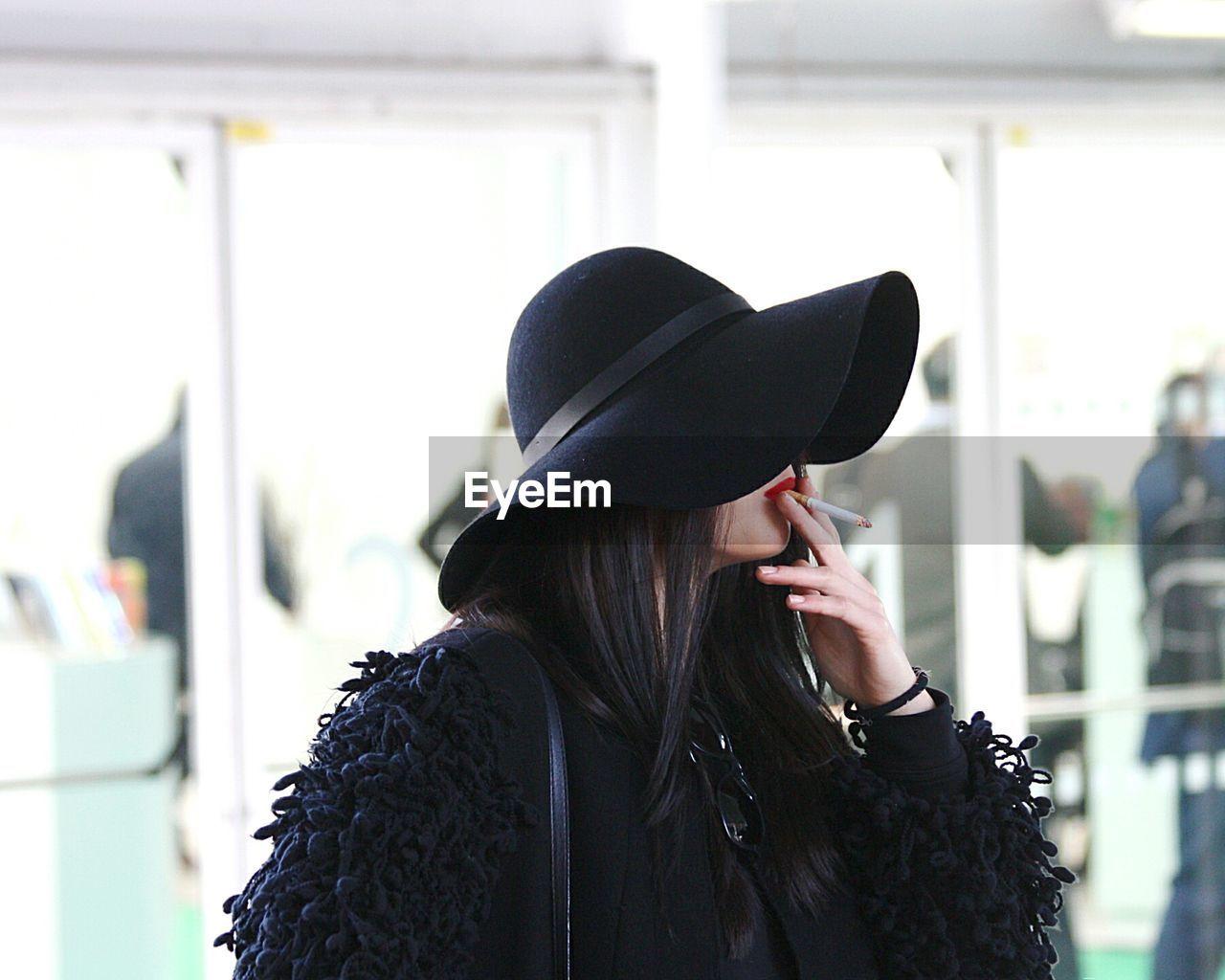 Woman wearing black hat smoking cigarette