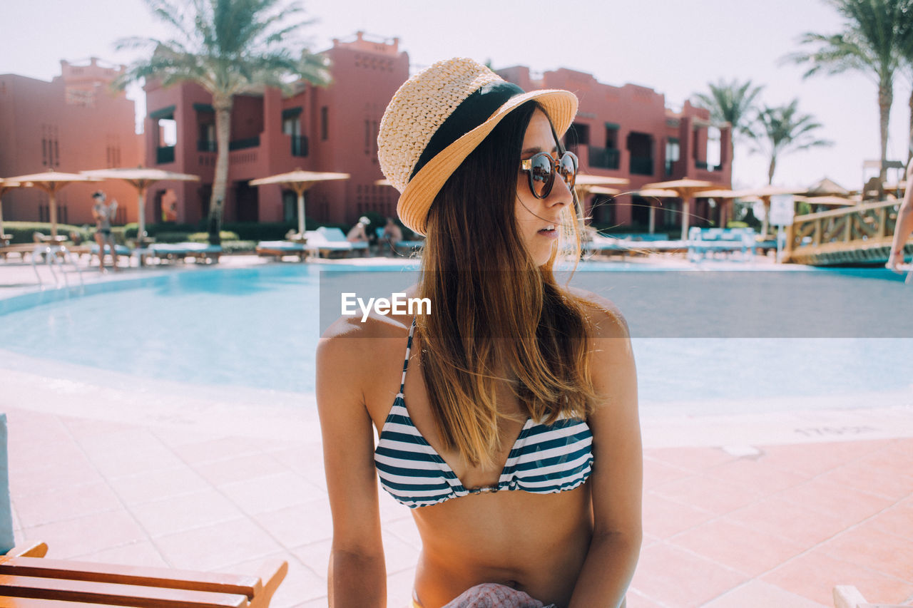 swimming pool, leisure activity, real people, water, one person, sunglasses, vacations, young adult, outdoors, young women, summer, long hair, day, lifestyles, built structure, sun hat, sitting, architecture, sunlight, building exterior, beautiful woman, palm tree