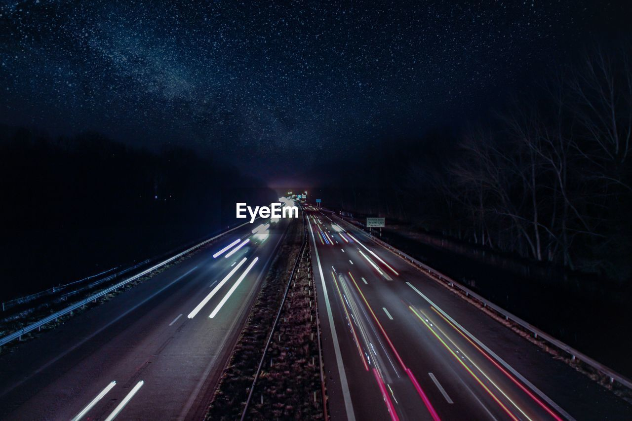 road, transportation, night, illuminated, motion, the way forward, long exposure, light trail, direction, highway, speed, sign, city, symbol, star - space, marking, sky, high angle view, no people, road marking, diminishing perspective, outdoors, multiple lane highway, astronomy