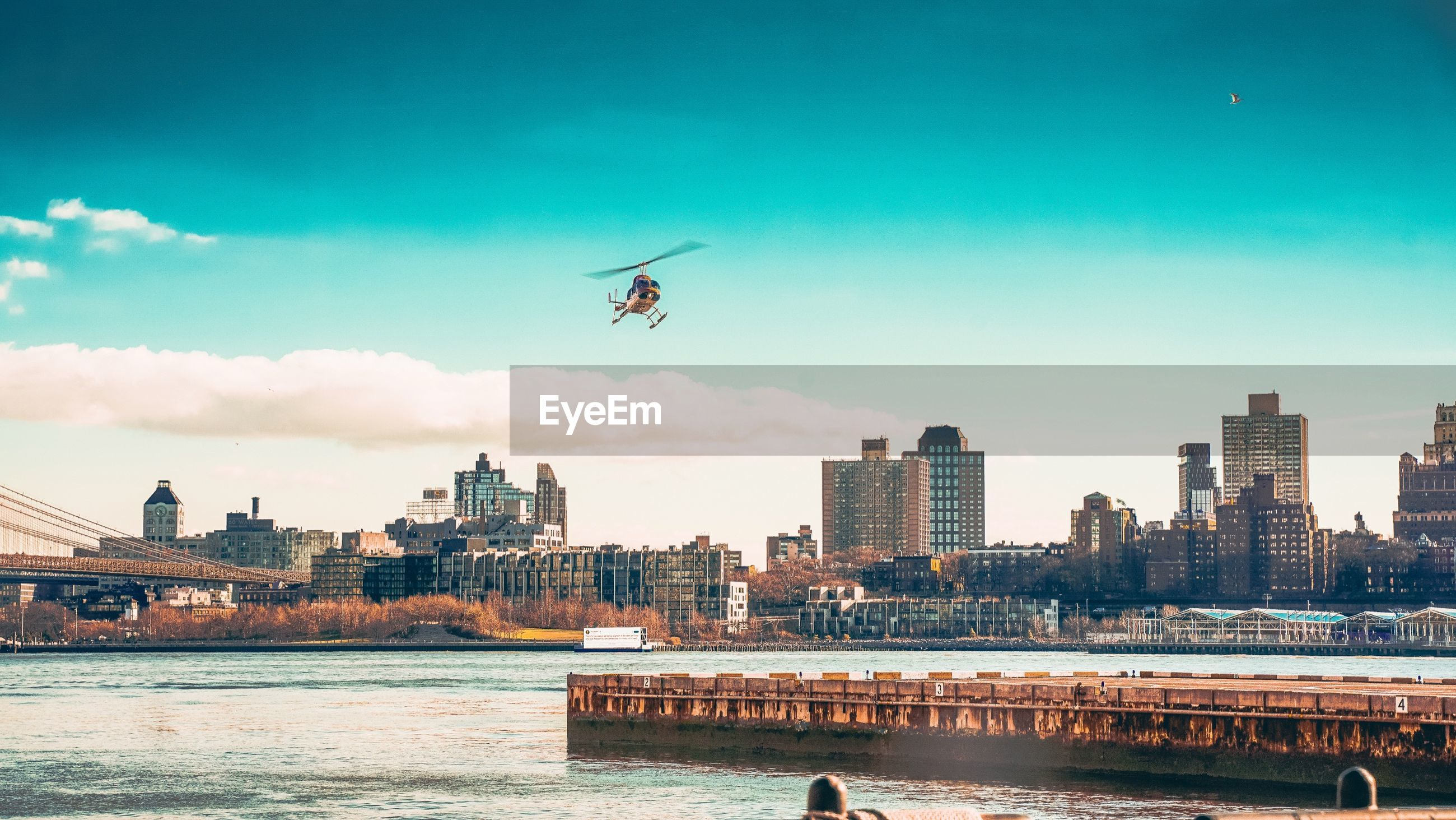 Helicopter flying over river in city against sky