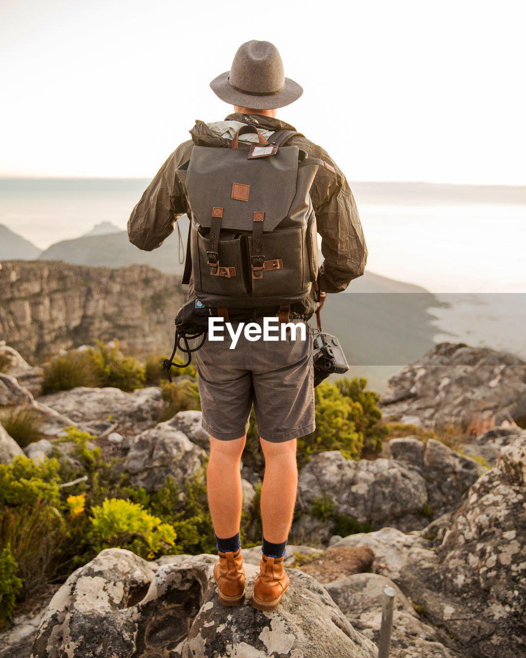 Full Length Rear View Of Man With Backpack Walking On Rocky Mountains Against Sea