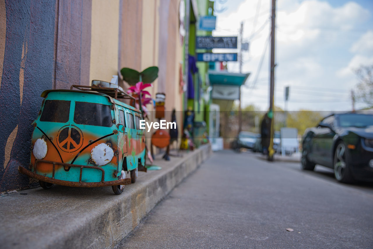 mode of transportation, transportation, car, land vehicle, motor vehicle, city, architecture, road, street, day, no people, built structure, building exterior, focus on foreground, outdoors, stationary, selective focus, sky, nature, creativity