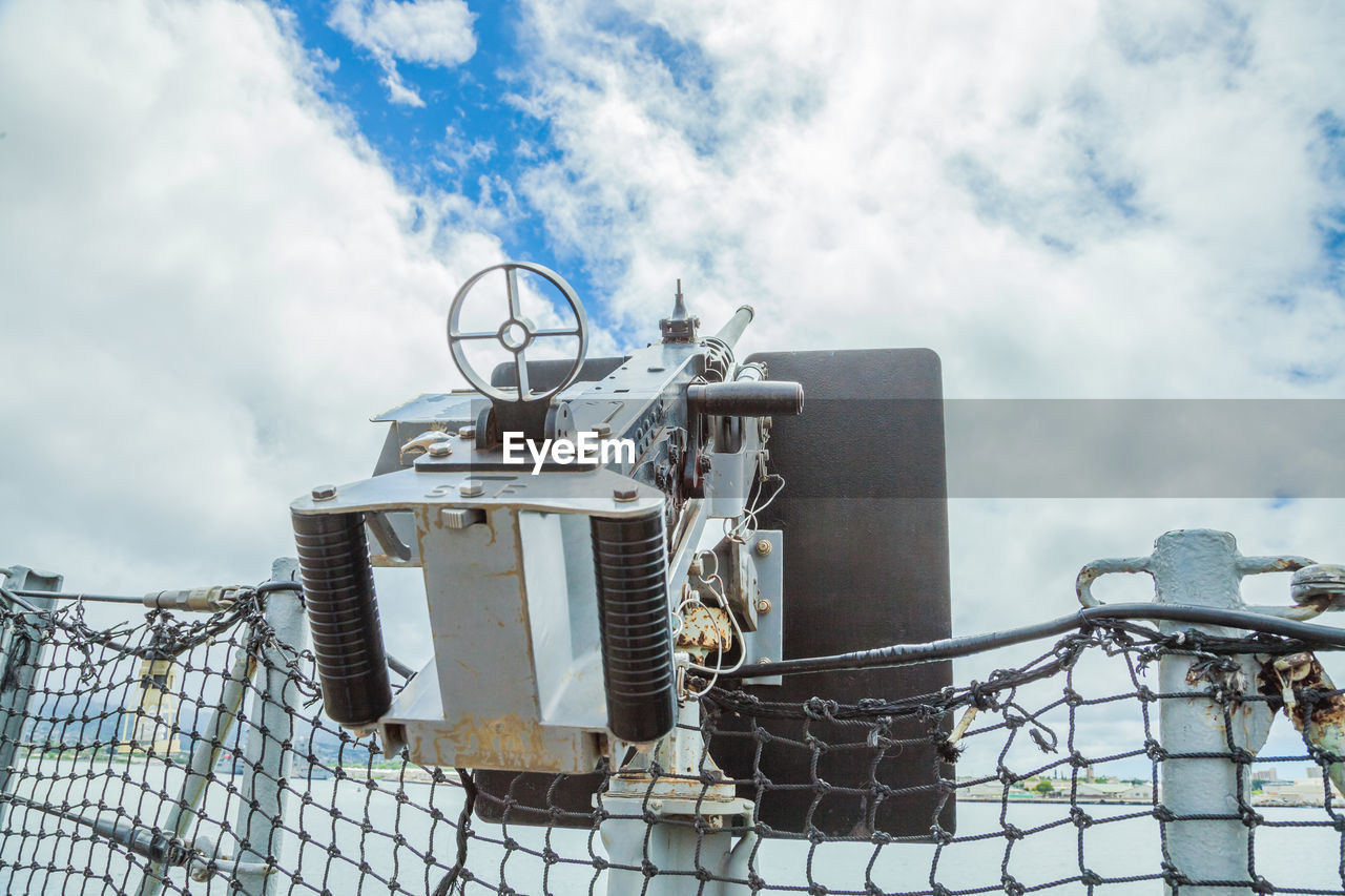 Low angle view of machinery against cloudy sky