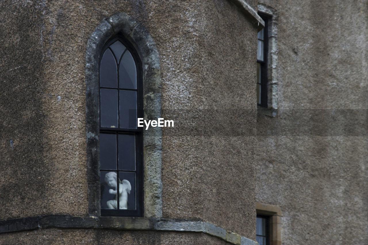 Angel Statue Seen Through Glass Window Of Historic Building