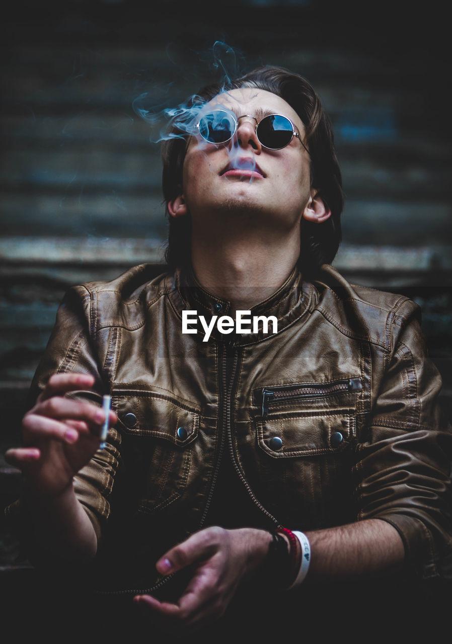 Man in sunglasses smoking cigarette