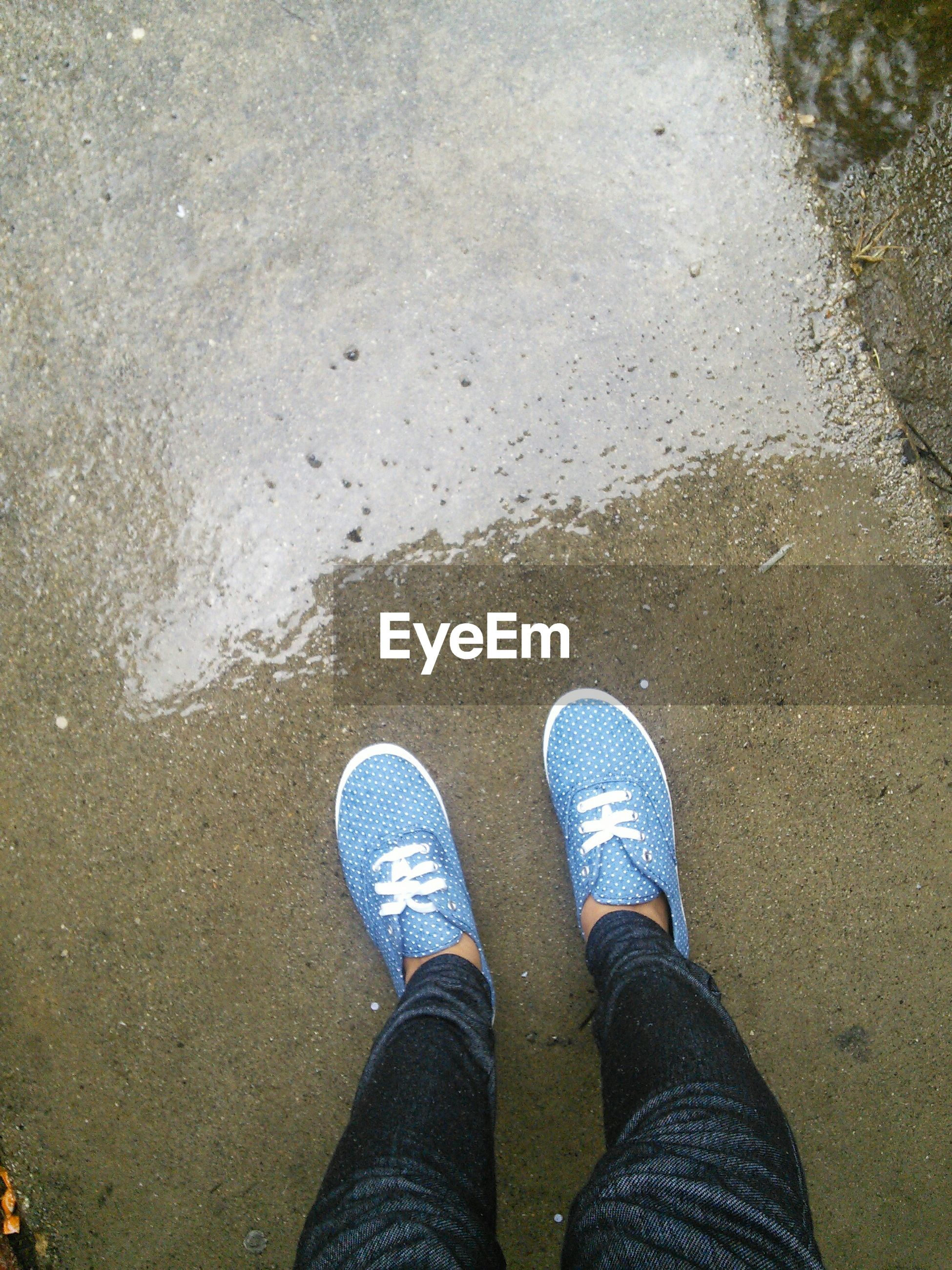 low section, person, personal perspective, shoe, standing, human foot, high angle view, water, lifestyles, footwear, wet, men, leisure activity, jeans, street, directly above, puddle