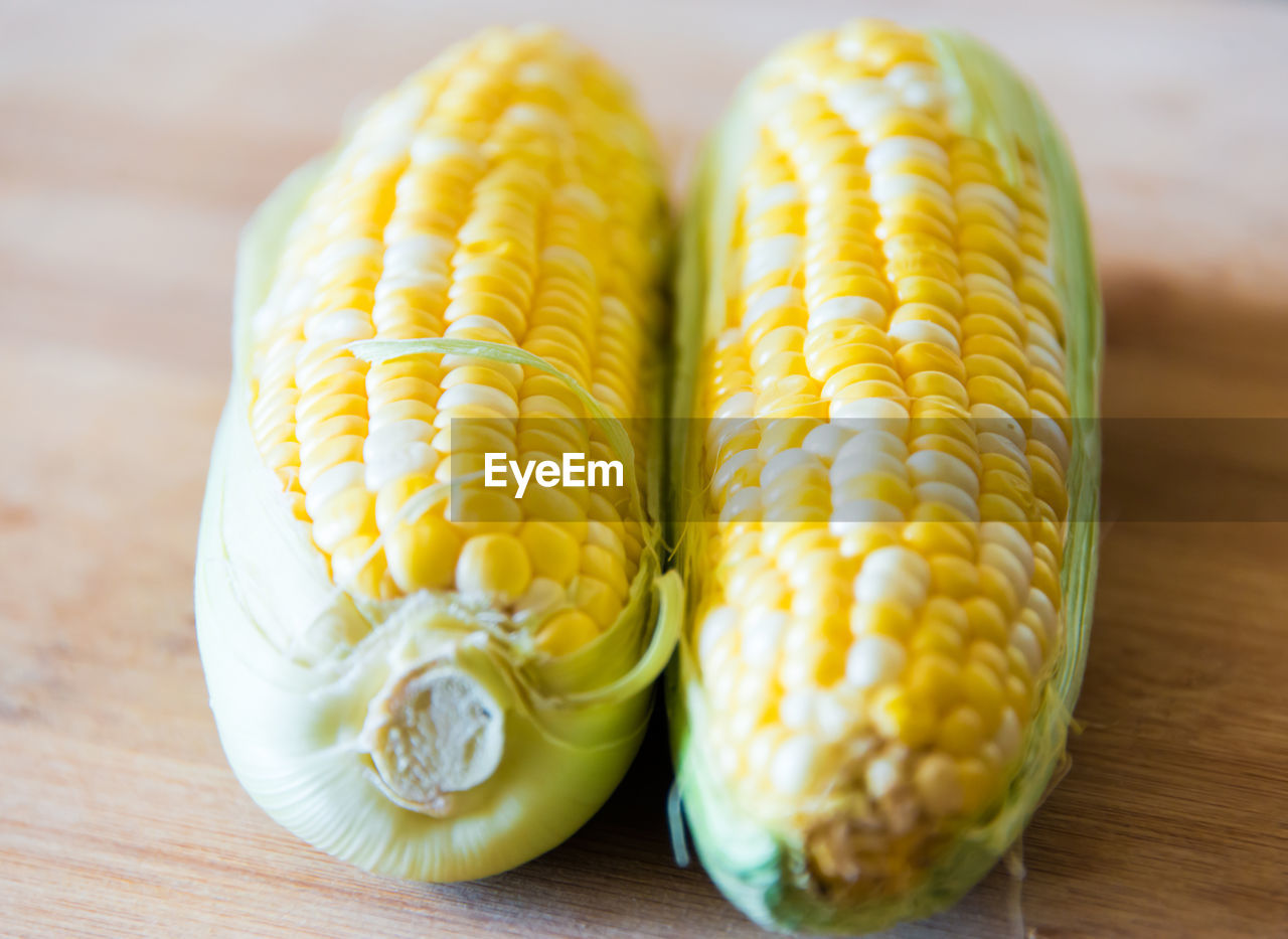 High Angle View Of Sweet Corns On Wooden Table