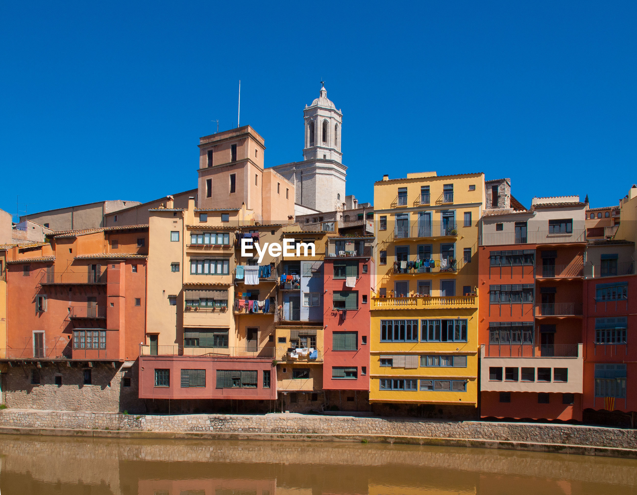Colorful buildings by river against clear blue sky