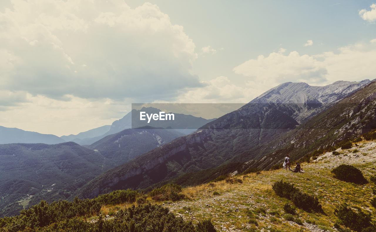 mountain, sky, cloud - sky, scenics - nature, beauty in nature, mountain range, tranquil scene, tranquility, non-urban scene, environment, nature, landscape, day, adventure, leisure activity, idyllic, activity, hiking, outdoors, plant, mountain peak