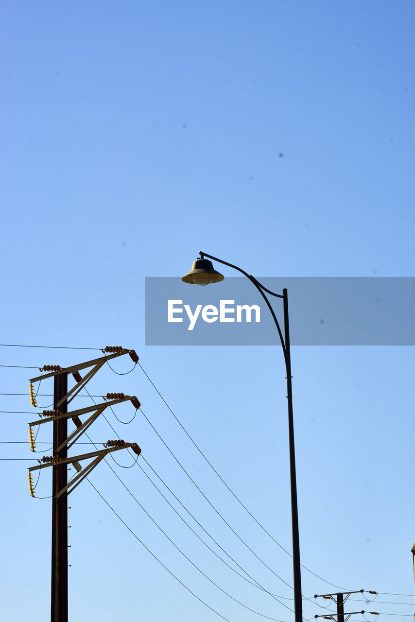 Low Angle View Of Power Line And Street Light Against Clear Blue Sky